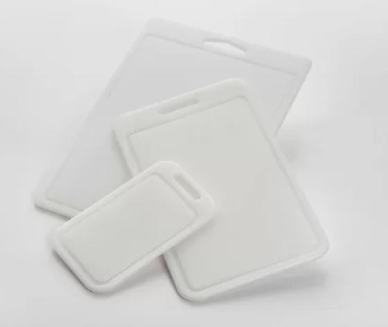 A set of white, plastic cutting boards that are dishwasher-safe.