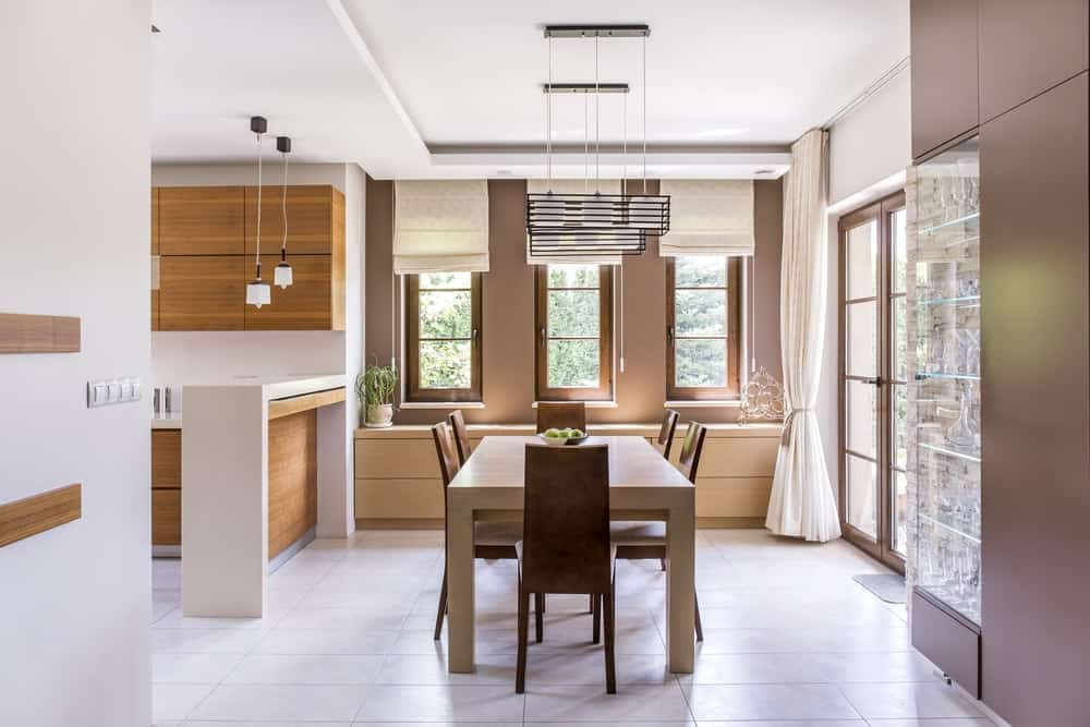 Kitchen and dining room in a modern house with light-colored window shades.