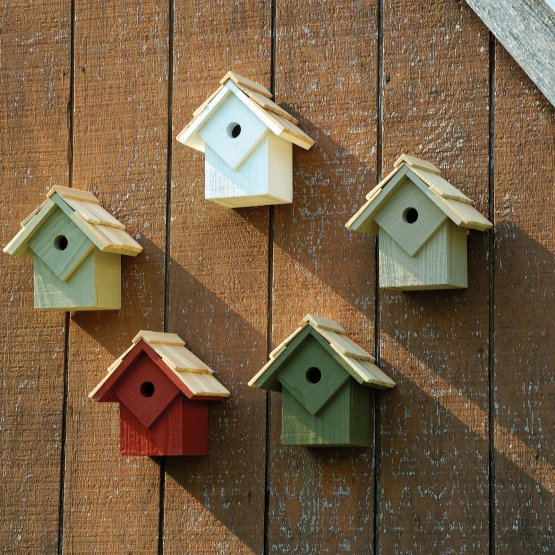 Five small wooden birdhouses of different colors, mounted to the wall.