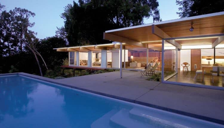 Hughes Umbanhowar Architects designed this Mid-Century modern style home in Southern California. The entire rear of the home is all glass looking out over a pool and trees.