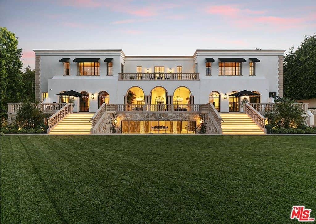 View of the home's backyard with perfect sprawling lawn and massive patio system.