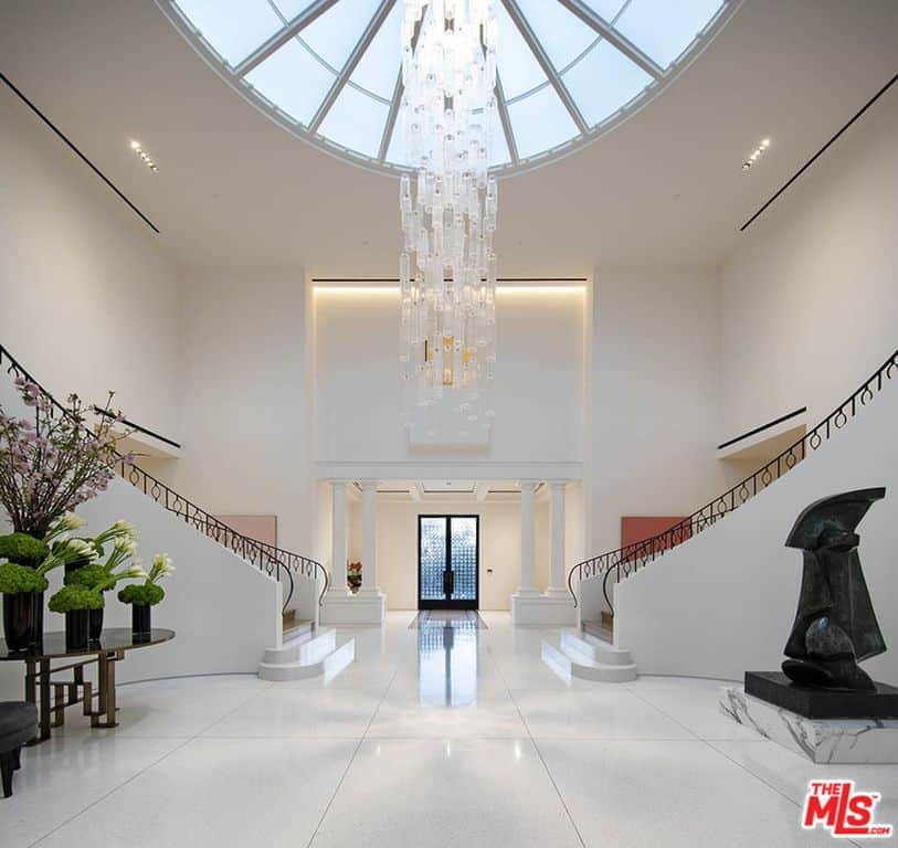 Huge white foyer with dome skylight, chandelier and massive white staircases.