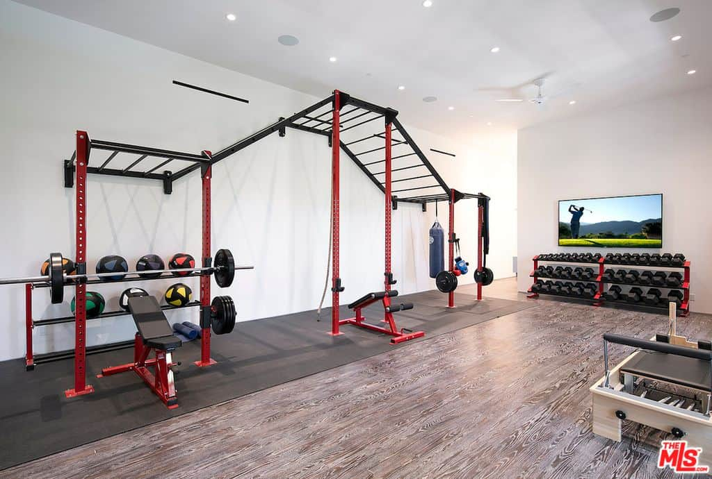 Large home gym with free weights, rack of dumbbells, wall-mounted TV and pilates equipment.