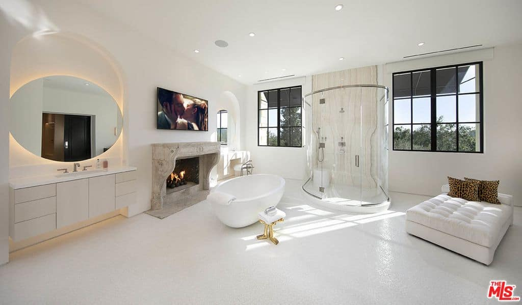Sumptuous white primary bathroom with fireplace, massive ottoman bed, oval glass shower and freestanding oval white tub.