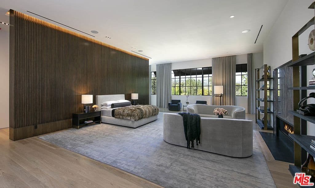 Enormous primary bedroom with wood accent wall, two sofas, fireplace and two armchairs creating a total retreat for rest, rejuvenation and relaxation.
