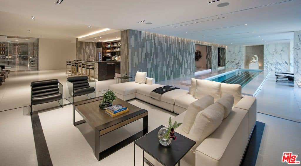 Large recreation area with sectional sofa adjacent to indoor pool.