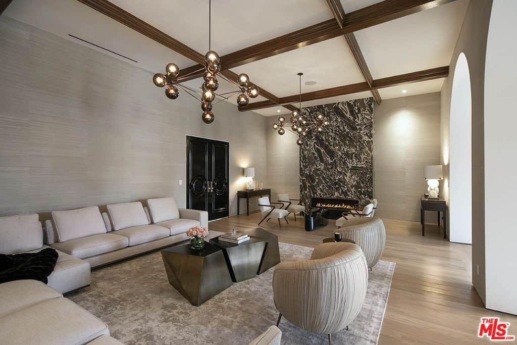 Living room with wood coffered ceiling, light wood floor, arched entry and huge light beige sectional sofa. Check out that spectacular glowing fireplace.