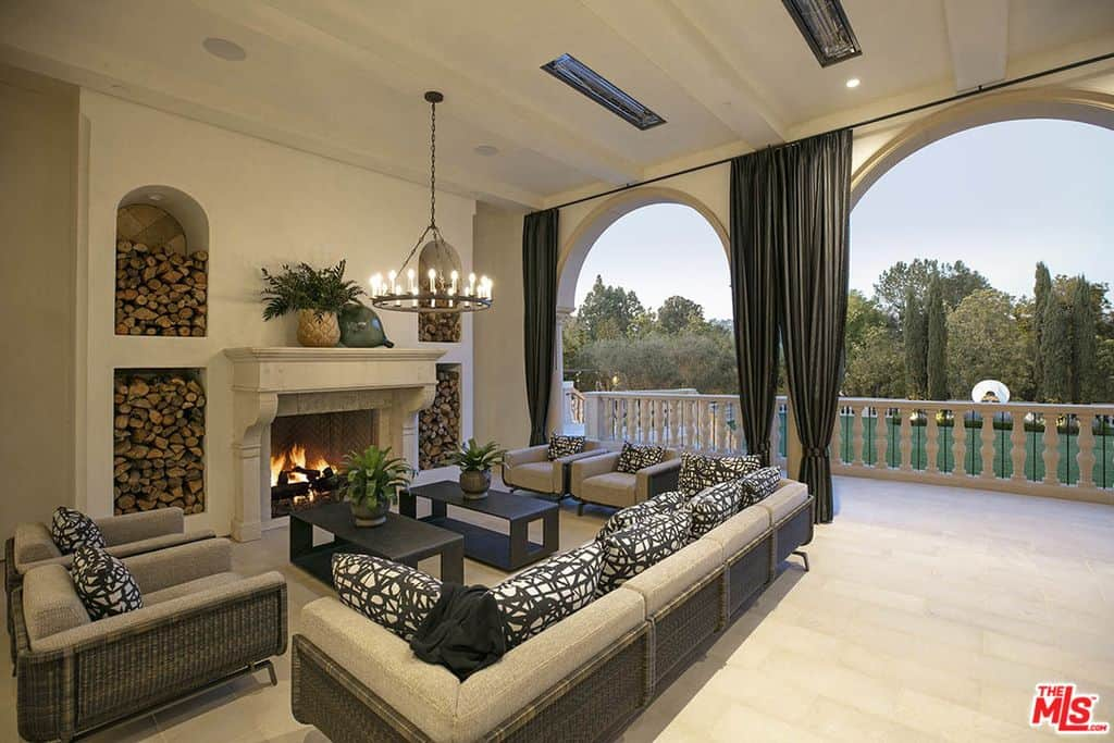Gorgeous outdoor covered patio with four patio armchairs, one long patio sofa all oriented to massive fireplace.
