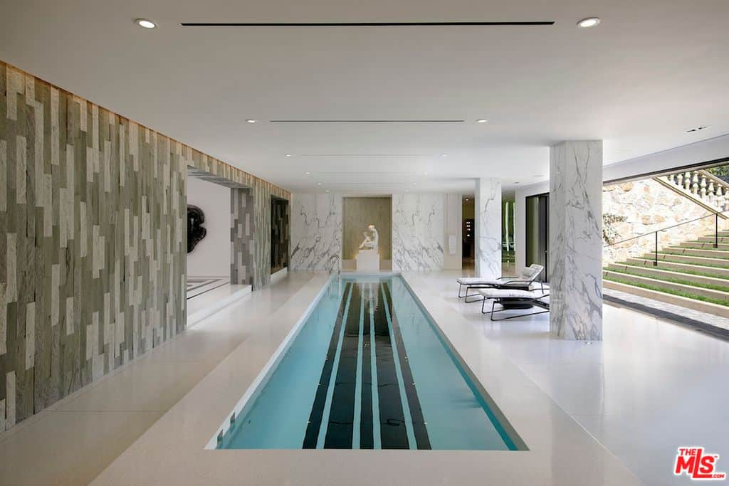 Close up of indoor swimming pool with open access to the grounds.