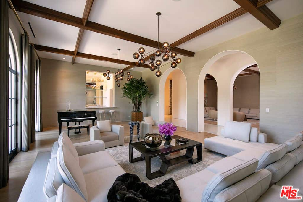 Large family room with huge u-shaped white sectional sofa, grand piano and bar accessed via multiple arched doorways.