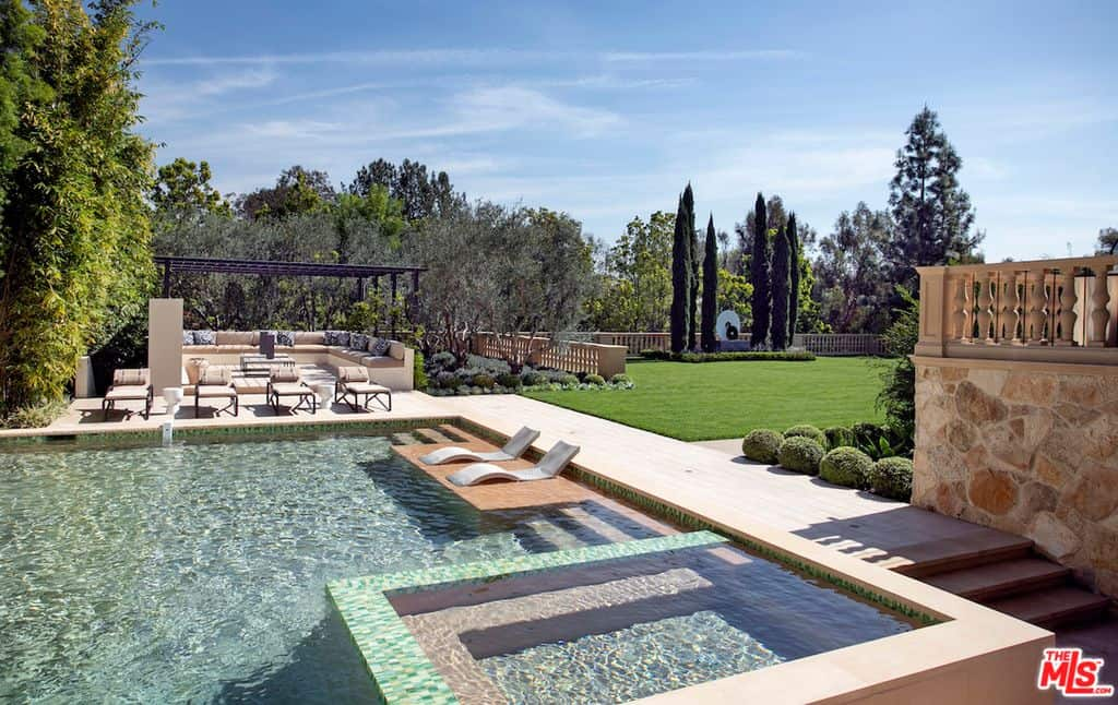 Large swimming pool adjacent to patio and sprawling lawn.