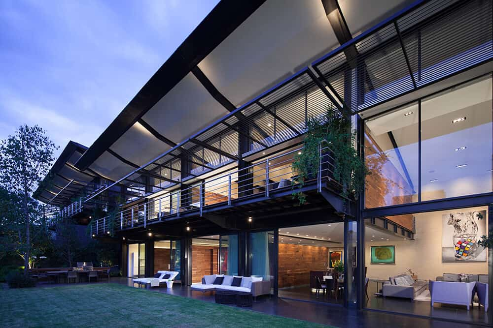 Modern steel and glass mansion with 3 stories of glass that stretches nearly the entire length of this massive home designed by Grupo Arquitectura.
