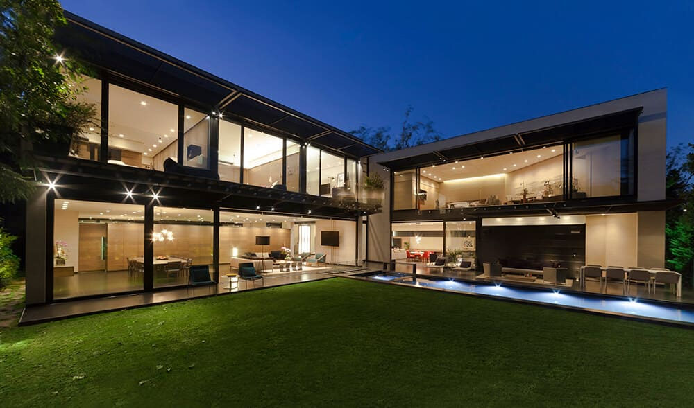 Large L-shaped modern mansion with absolutely massive windows along both wings overlooking the property. Designed by Grupo Arquitectura.