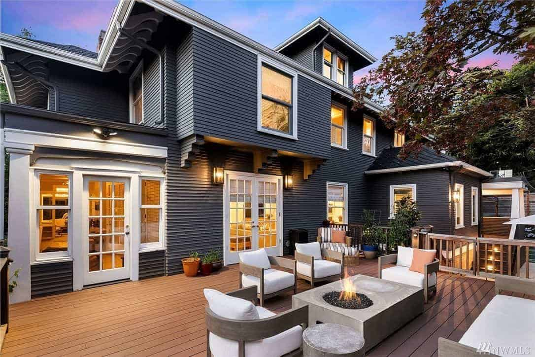 This black home with a wooden exterior boasts a beautiful deck with a living set and a fire pit.