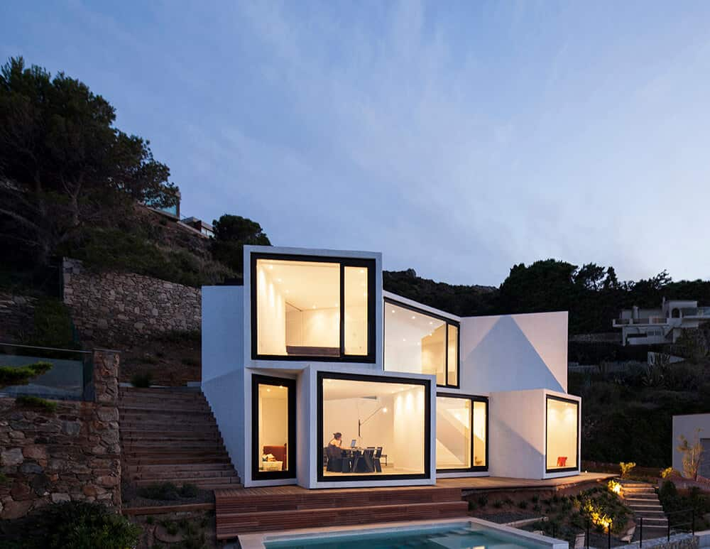 Talk about clever hillside home design. I love how the sections point in different directions. Each section delineated by huge windows. Designed by Cadaval & Solà-Morales.