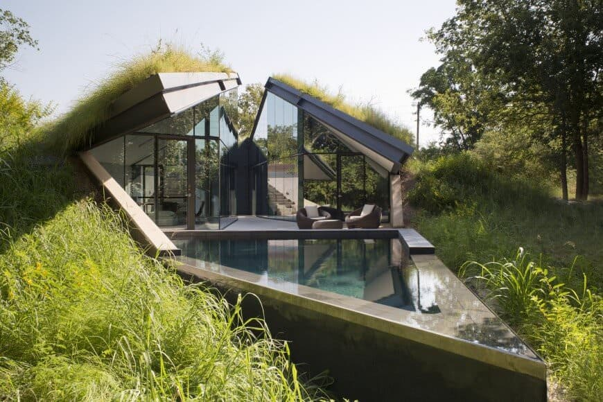 Fascinating geo-shaped house with loads of glass whee the remaining sides/roof is a grass roof. Very smart design and it looks cool too. I love how the home opens up seamlessly to the small triangle pool. Designed by Bercy Chen Studio.