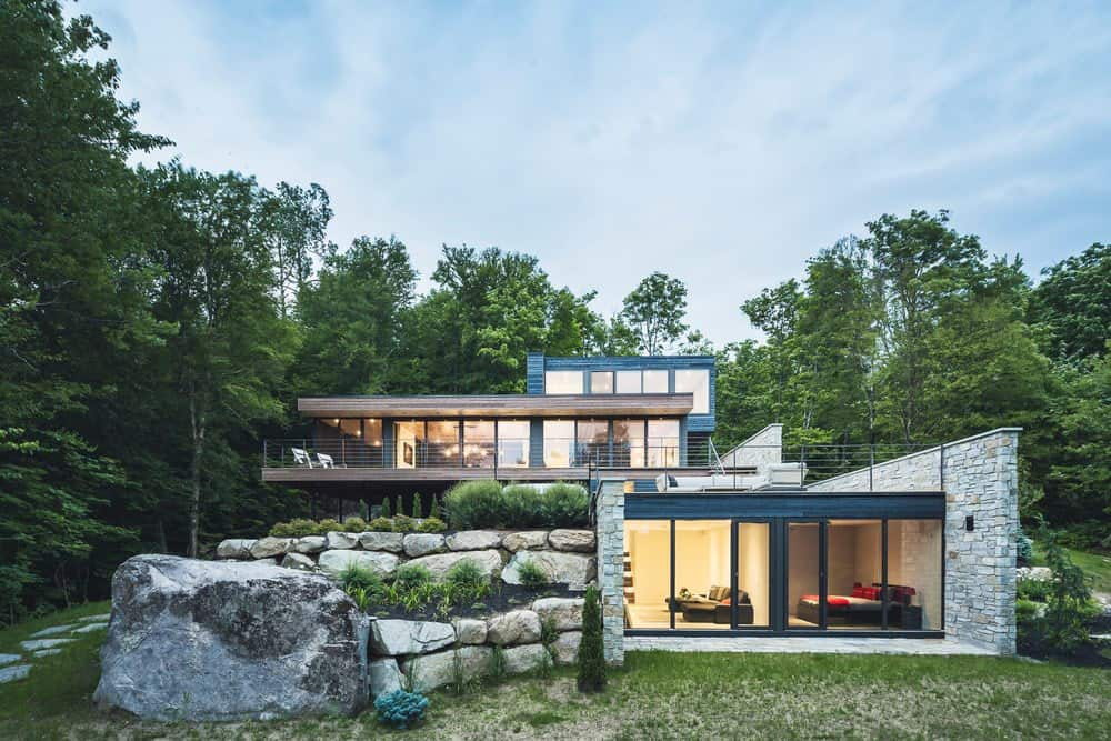 Modern contemporary house accented with a boulder retaining wall in the middle of an enchanting forest. The house exterior creates a harmonious design with its environment.