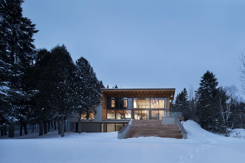 Snowy paradise home on large property with huge amount of glass looking out over the property. Designed by Bourgeois Lechasseur Architectes.