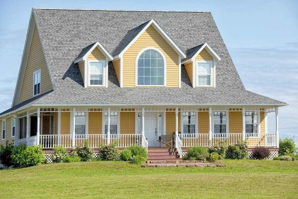 A dark paint on the shingles is more weather-resistant than its lighter counterparts but it also makes this roof appear even larger. The visual weight is offset by the yellow exterior siding while white trims make its grand appearance on the classic porch.