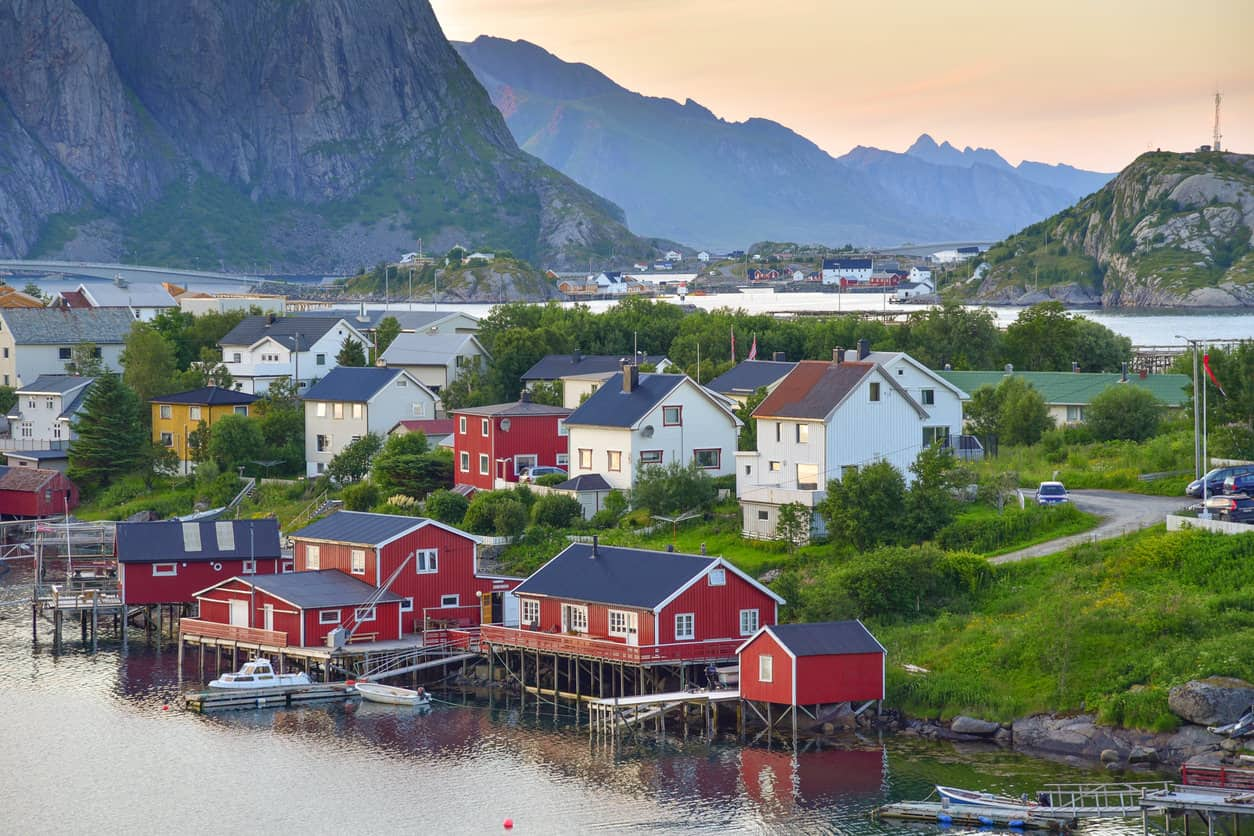 View of Lofoten Islands in Norway peppered with red and white houses.