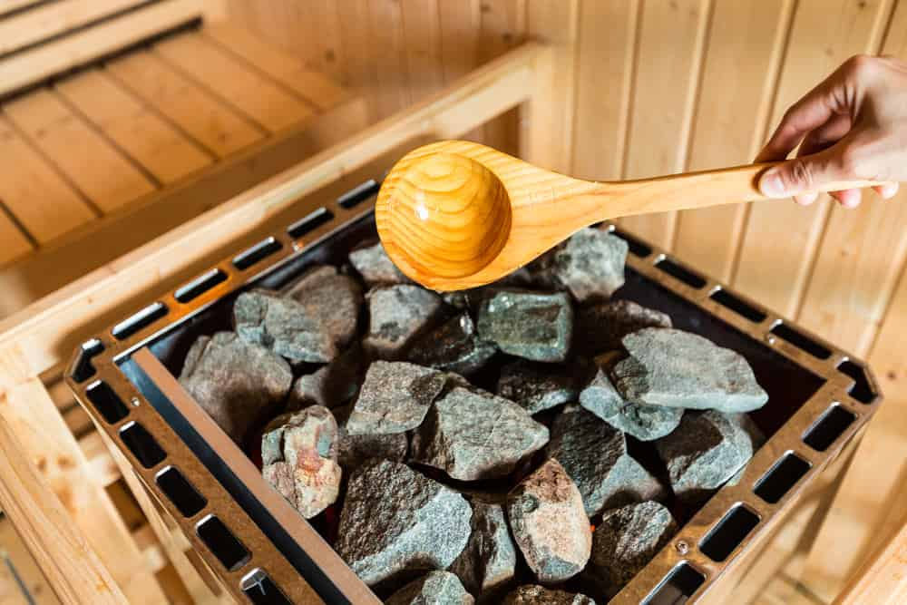 Wood ladle pouring water on hot sauna rocks