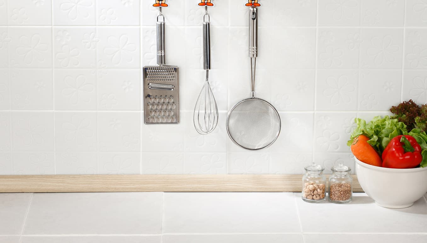 Kitchen cooking utensils on hooks against tile wall