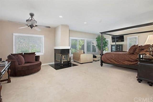 The large master suite offers a carpet flooring, sitting spaces, fireplace and a TV.
