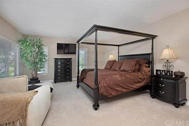 The bedroom offers a king size bed and a carpet flooring along with a sitting space, TV and a fireplace.