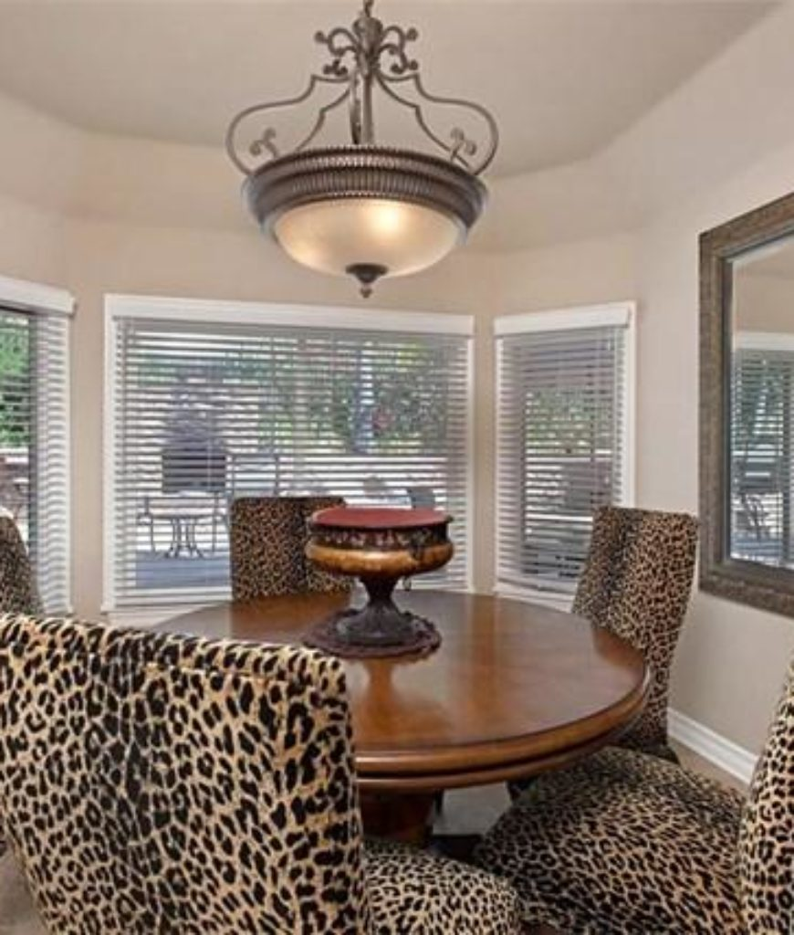The dining nook features a stylish round table and seat set lighted by a pendant light.