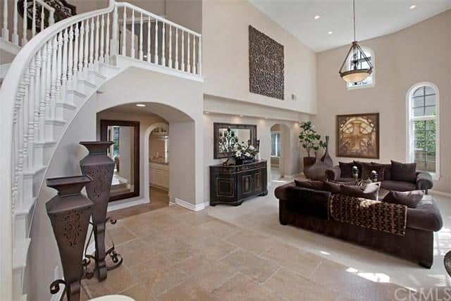 This foyer boasts a sofa set lighted by recessed lights and a pendant light. The high ceiling looks perfect.