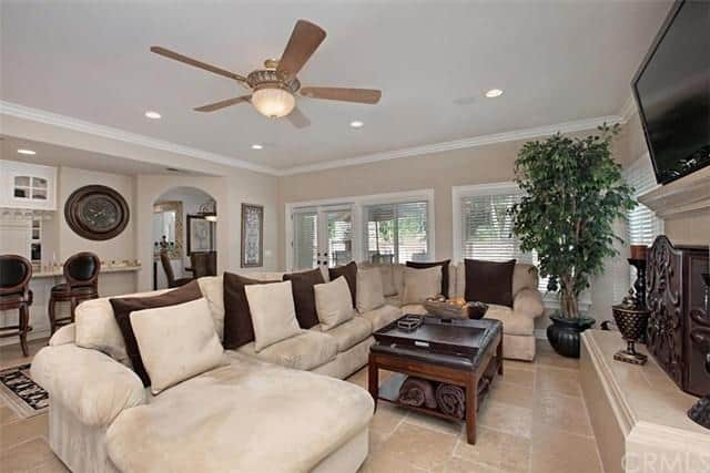 The family room offers a white long couch and a fireplace along with a TV.