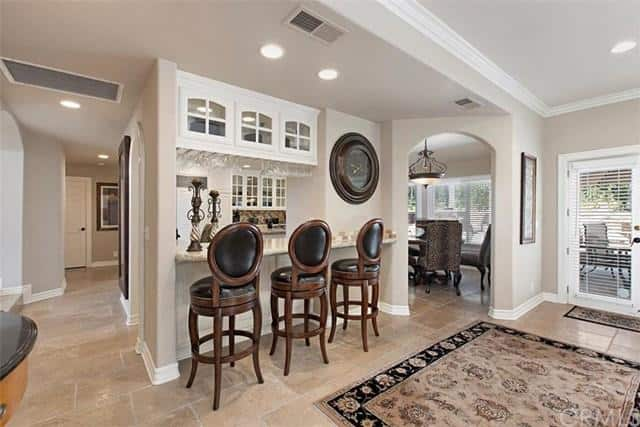 There's a breakfast bar in the home too featuring a classy bar seats lighted by recessed ceiling lights.