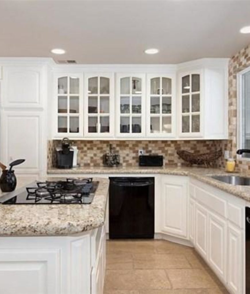 The kitchen features granite countertops with white walls and cabinetry.