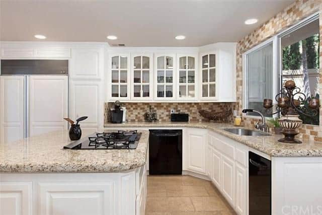 The Kitchen Features Granite Countertops With White Walls And Cabinetry