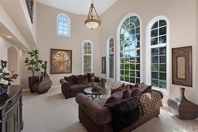 The formal living room features a two-storey high ceiling and a carpet flooring along with elegant furniture set.