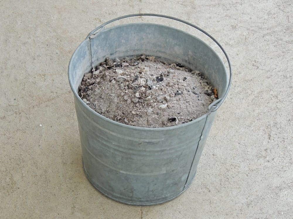 A metal bucket with ash inside.