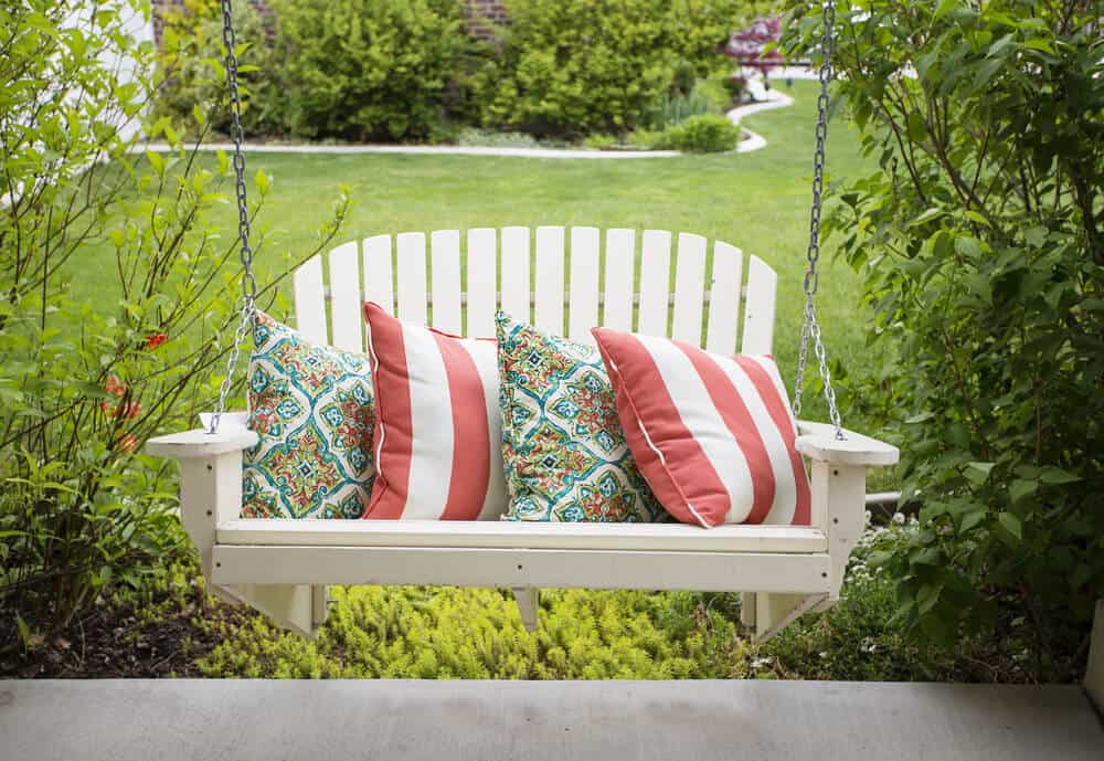 A white, wooden swing with stylish throw pillows, on a back yard.