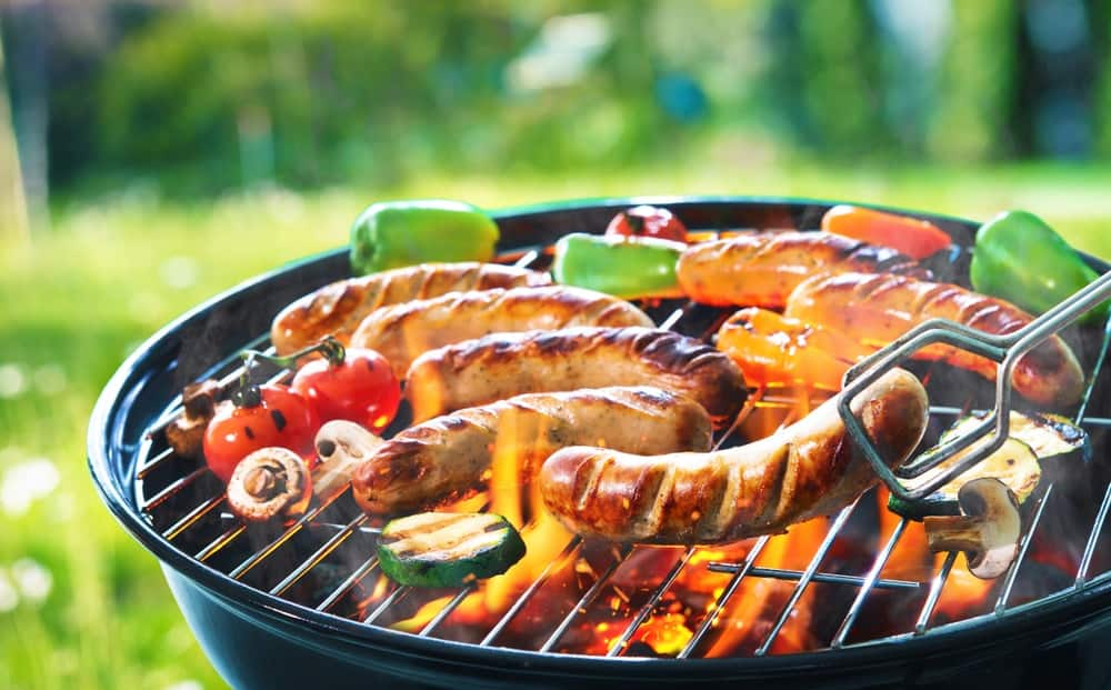 Grilling sausage on an electric flaming grill outdoors.