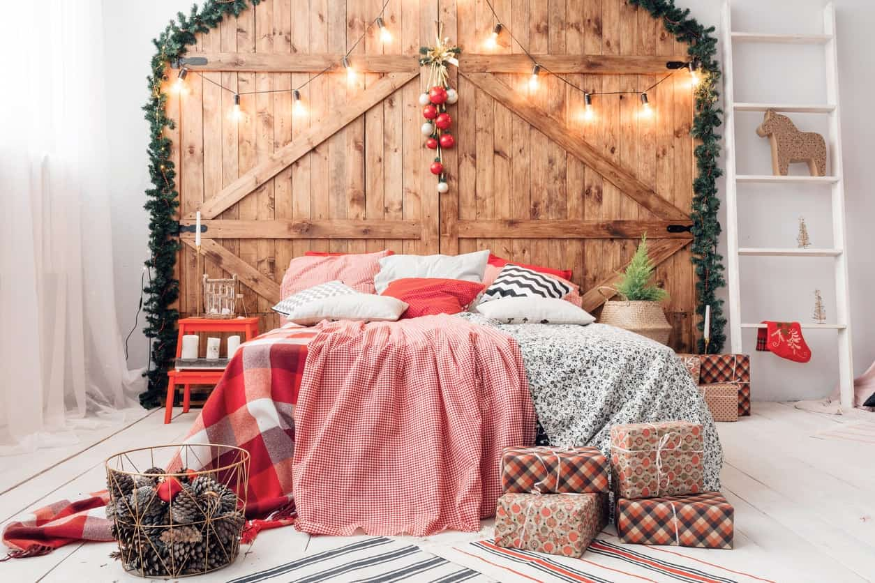 White bedroom decorated for the Christmas season with large barn door used as headboard , string lights, a ladder, gifts, and white wooden flooring.