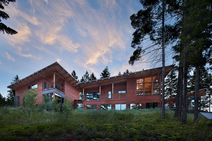 A large modern house featuring a red exterior and is surrounded by mature trees.