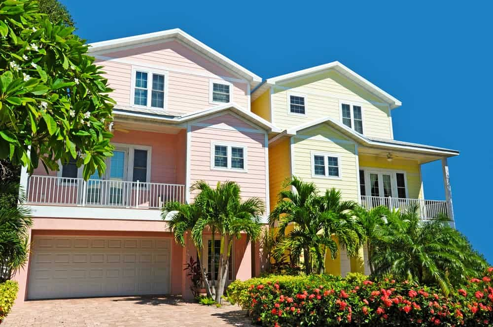 These pink and yellow beach houses with white trims inject a dose of happy vibes that's perfect for a summer getaway. The clear blue sky and tropical plants hint the idea of a tropical paradise.