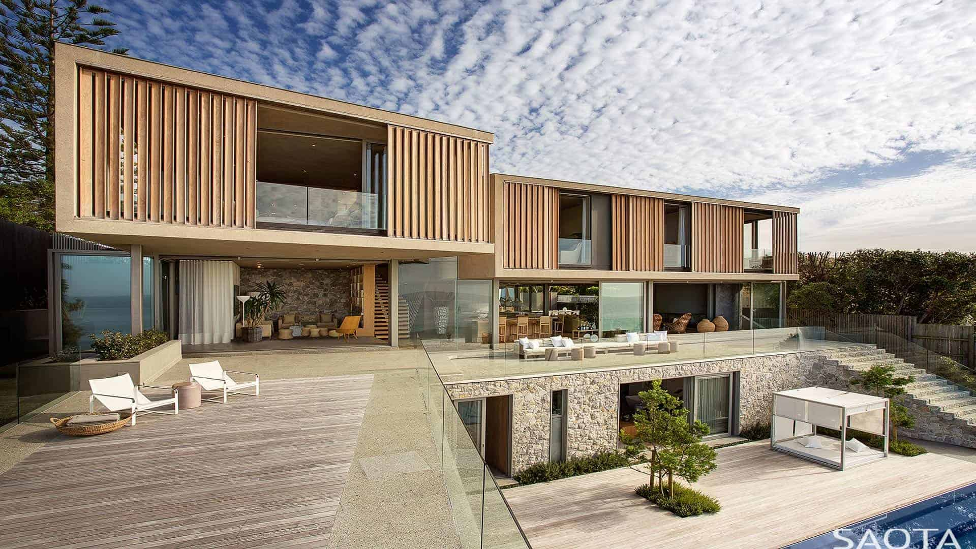 A sprawling modern house featuring a large outdoor area with a swimming pool.