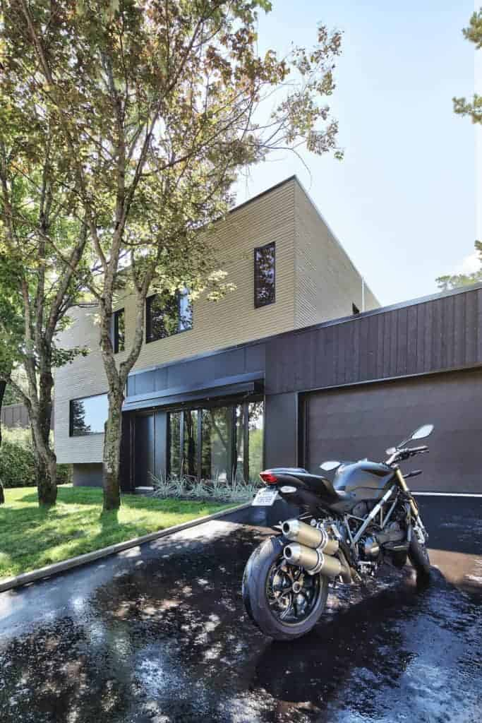 A beautifully renovated home with a wooden exterior and has a straight driveway leading to the garage.