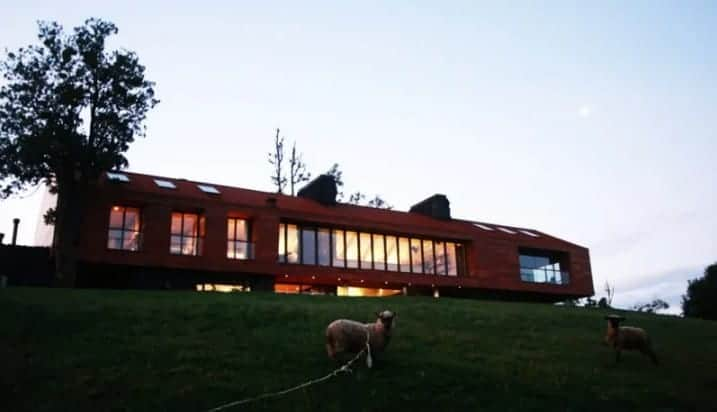A gorgeous rustic lodge with glass windows and offers a stunning view of the surroundings.