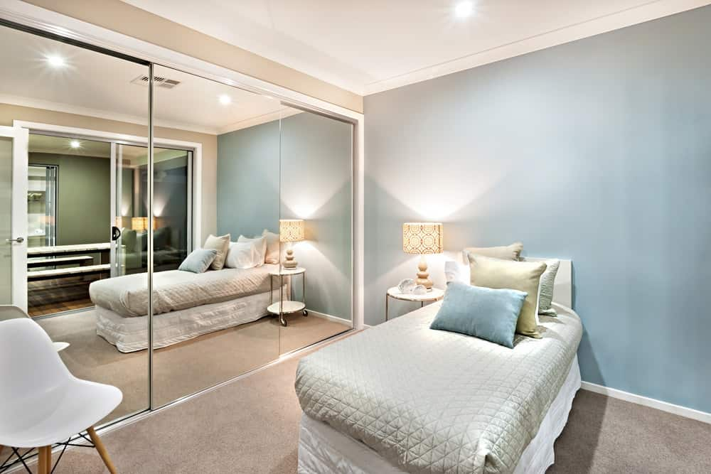 Bedroom with sky blue walls and a floor to ceiling mirror.