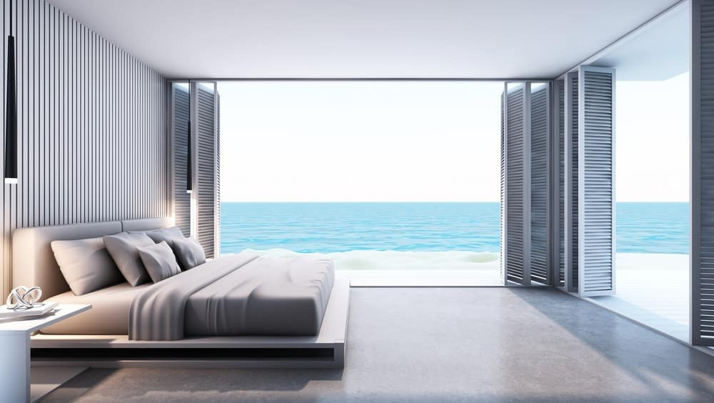Modern bedroom with king size bed and stylish walls. It overlooks the beautiful ocean view.