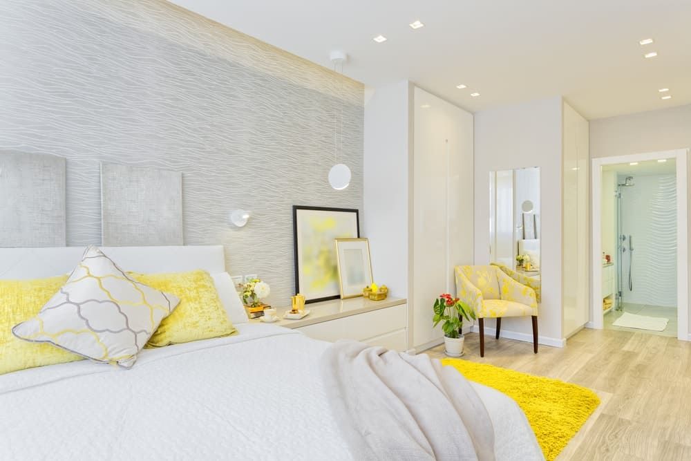 Primary bedroom with white walls and yellow accent along with scattered recessed lights.