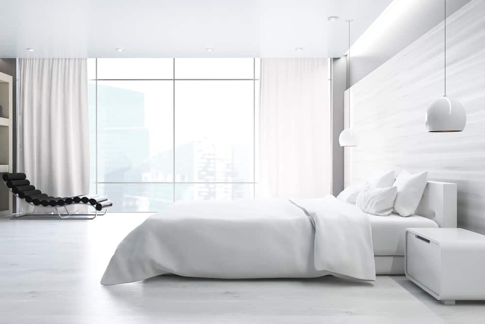 Modern bedroom with pure white theme and floor to ceiling glass windows.