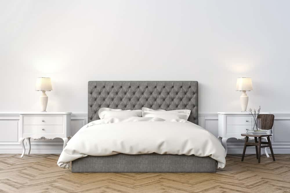 Large white bedroom with gray bed frame and two side tables on both side with lamps.