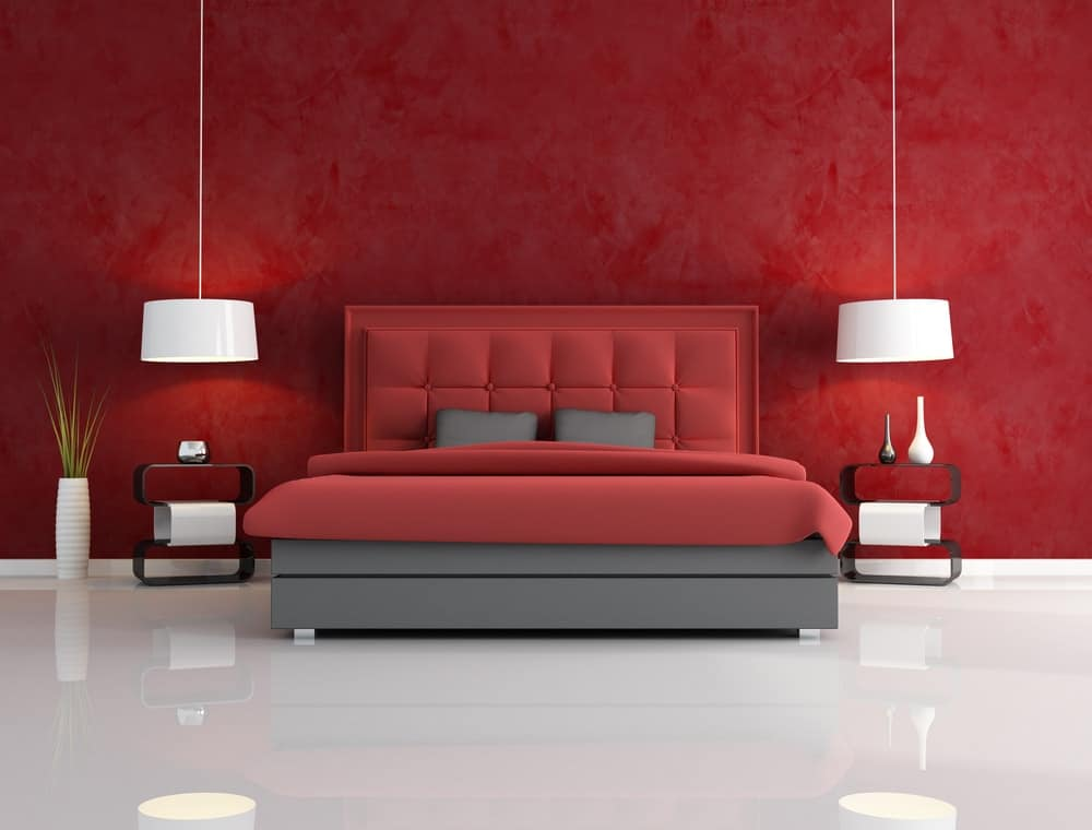 Contemporary bedroom with red walls and bed along with smooth white flooring and pendant lamps.